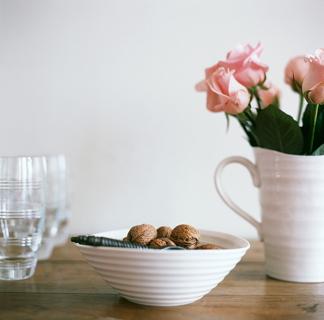 Pink roses in a jug, a bowl of walnuts and glasses