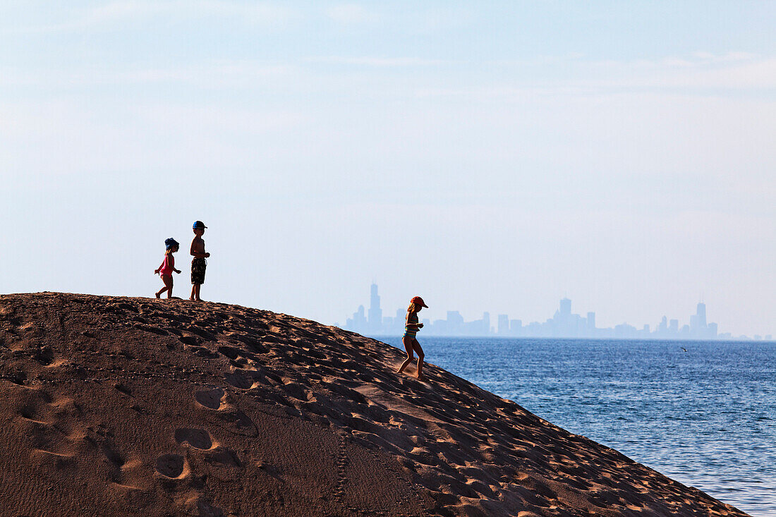 Kids standing on a sand dune in Indiana Dunes National Lakeshore park, silhouette of Downtown Chicago in the background, Indiana, USA