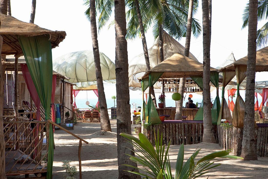 Beach resort with solar sails, bar and bungalows on the beach, Agonda, Goa, India