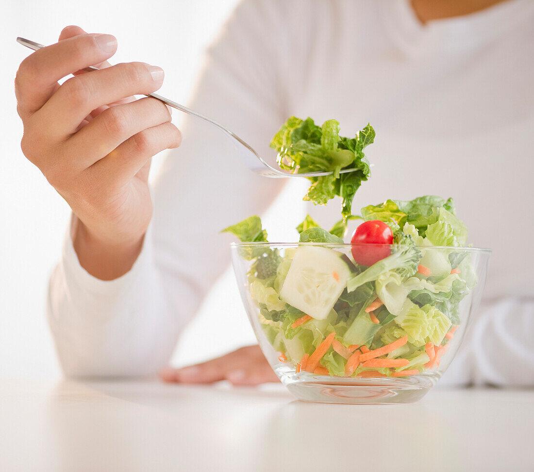Mixed race woman eating salad, Jersey City, New Jersey, USA
