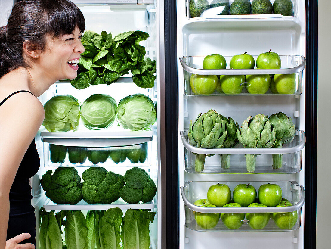 Mixed race woman looking at green vegetables in refrigerator, Los Angeles, California, United States