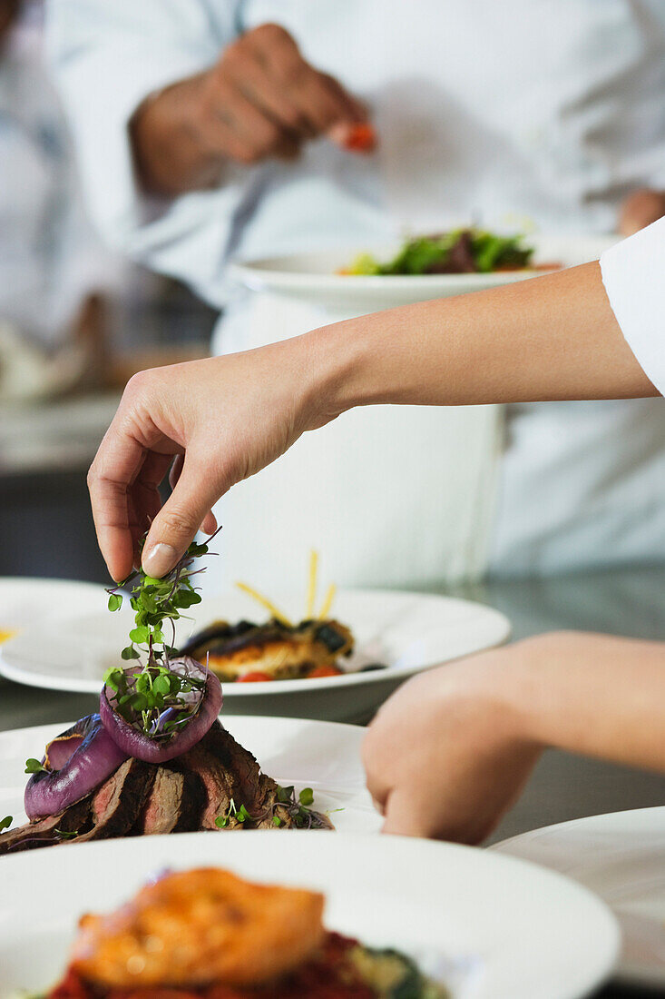 Chef putting garnish on plate of food, Orlando, FL