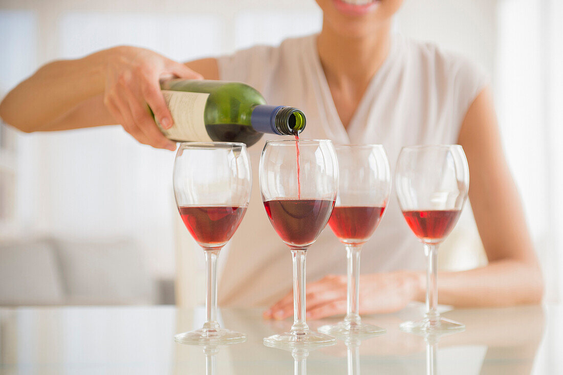 Black woman pouring glasses of wine, Jersey City, New Jersey, USA