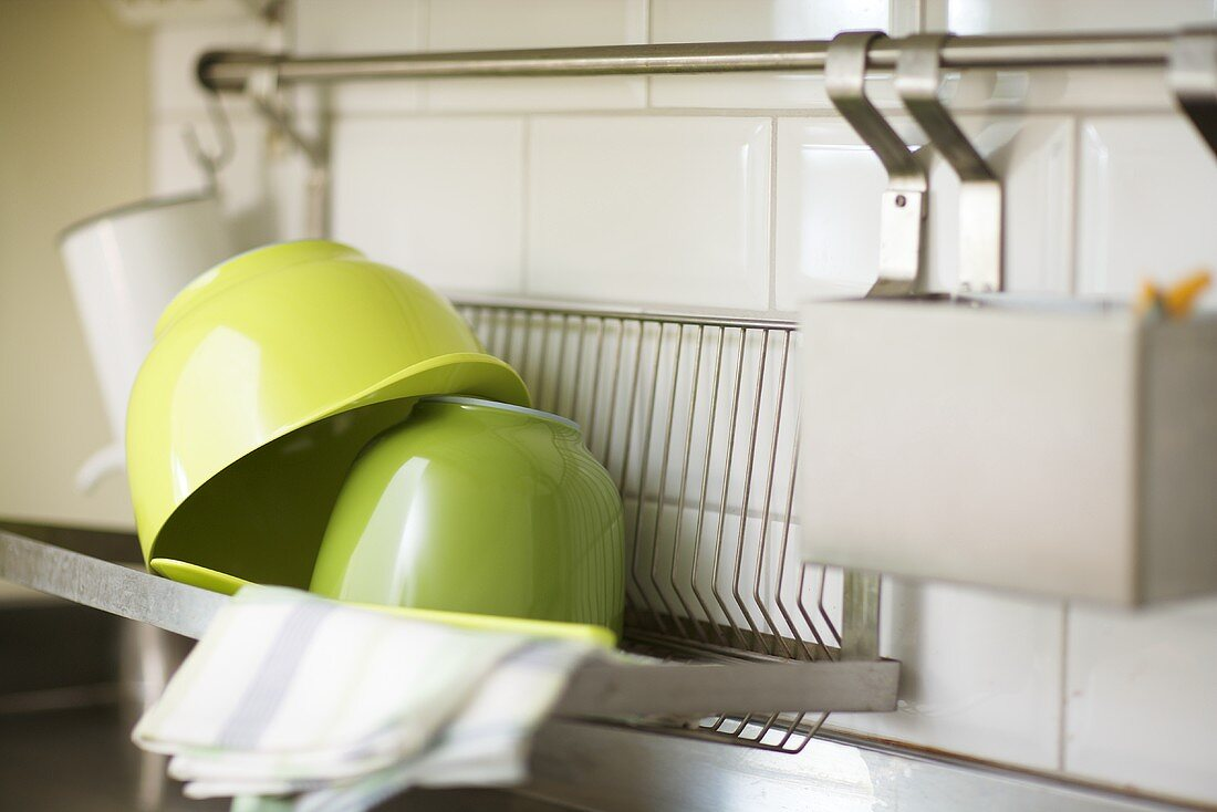 A green bowl on a drainer against a white tiled wall
