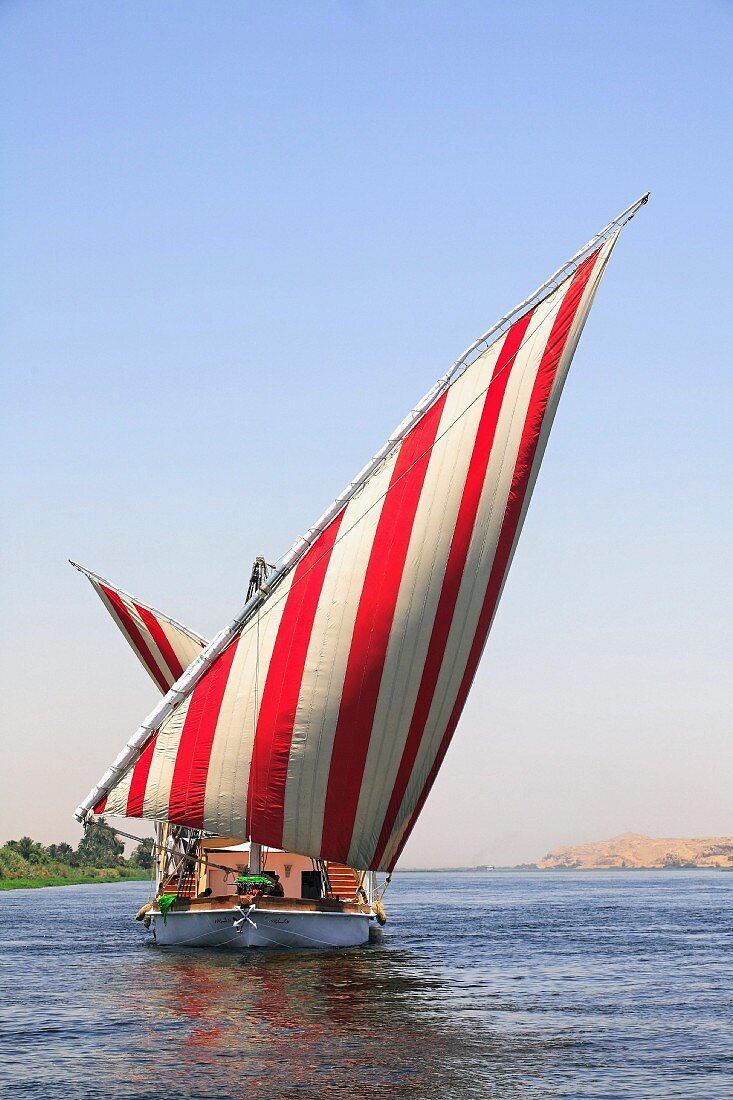 A sailing boat with red and white striped sails on the River Nile, Egypt