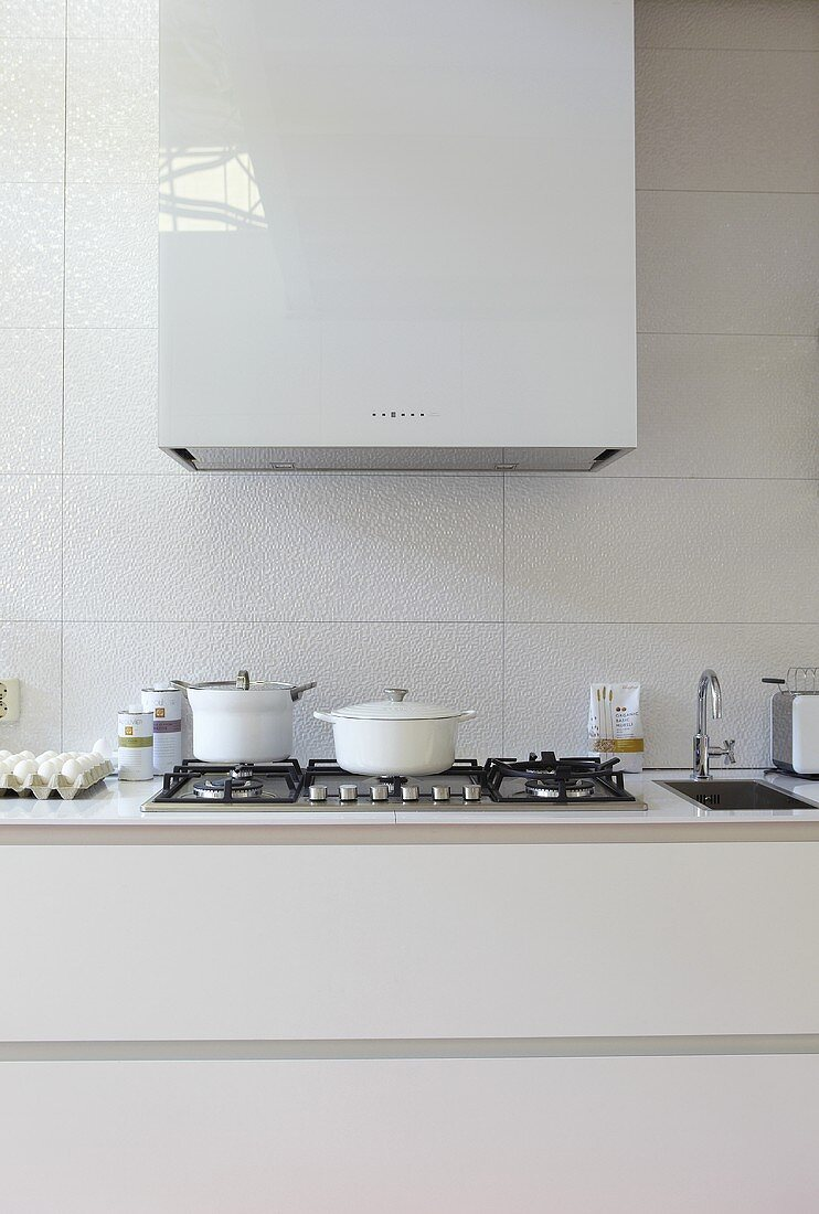 White pots on a gas hob with an extraction hood