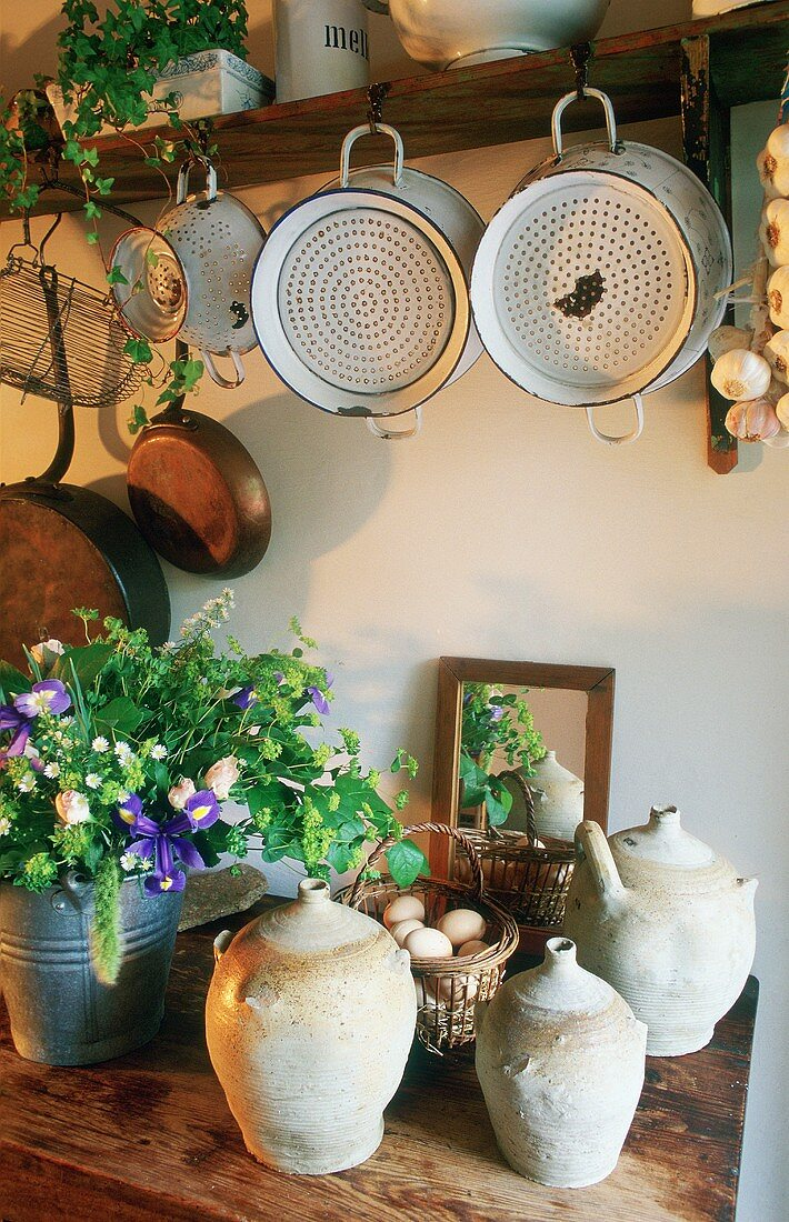 Antique metal colanders hanging from a shelf and handmade clay pots on a wooden shelf below