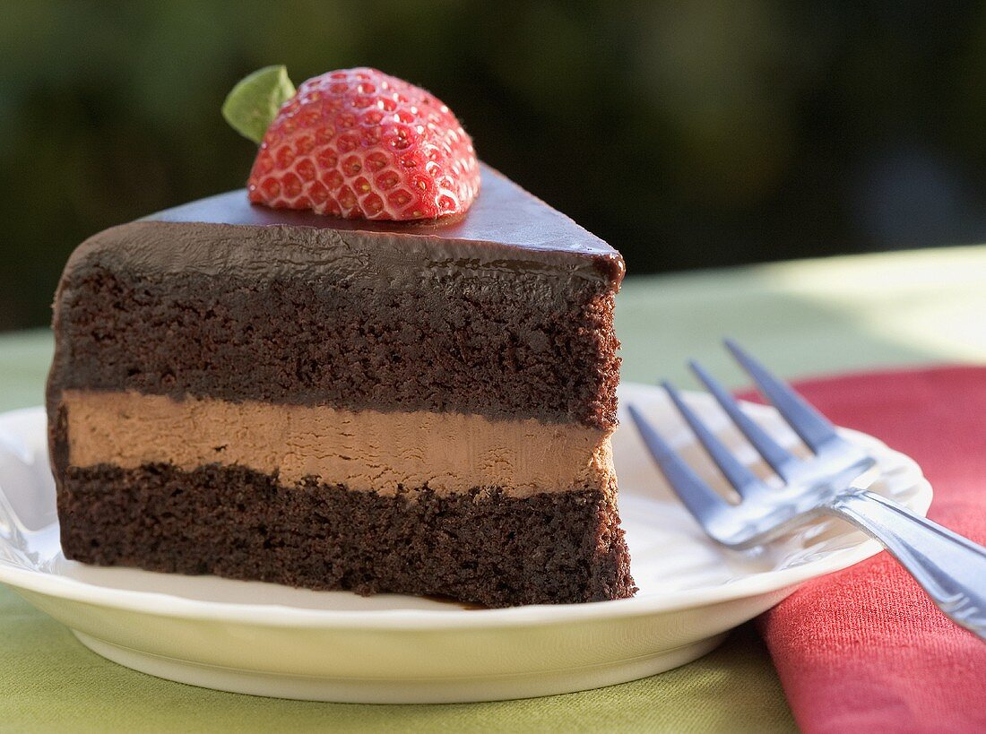 Slice of Layered Chocolate Cake Topped with a Strawberry