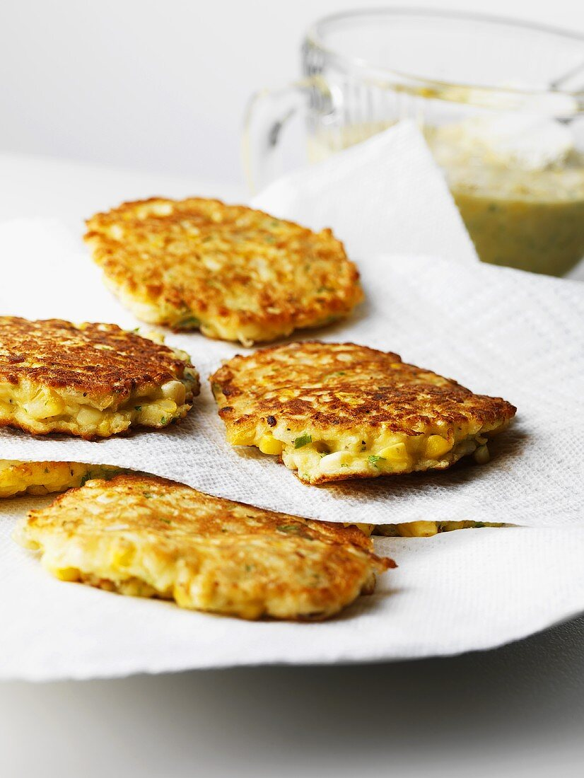 Layers of Corn Fritters Cooling on Paper Napkins; On a Plate