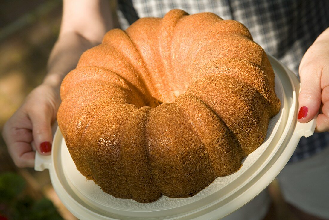 A Woman Holding a Bundt Cake, Outdoors