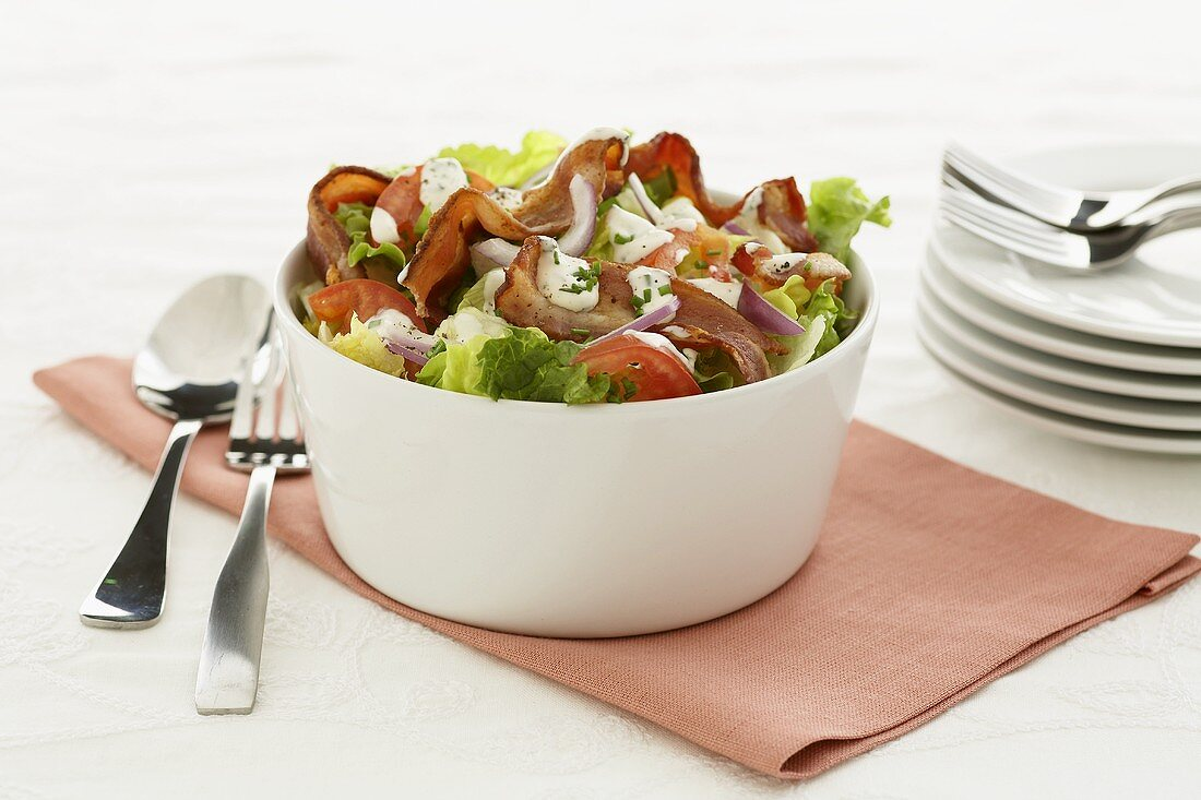 Salad leaves with bacon, tomatoes and red onions