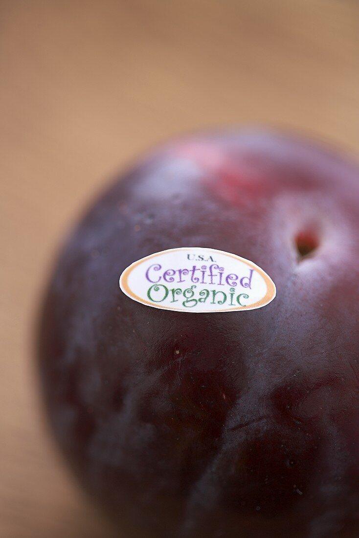 An Organic Plum with Sticker; Close Up