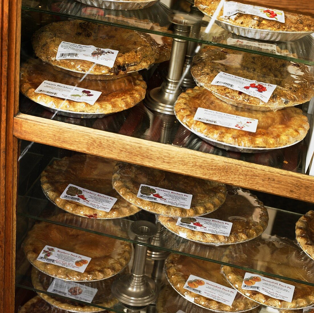 Assorted Sweet Pies in Packaging Displayed in a Bakery Case