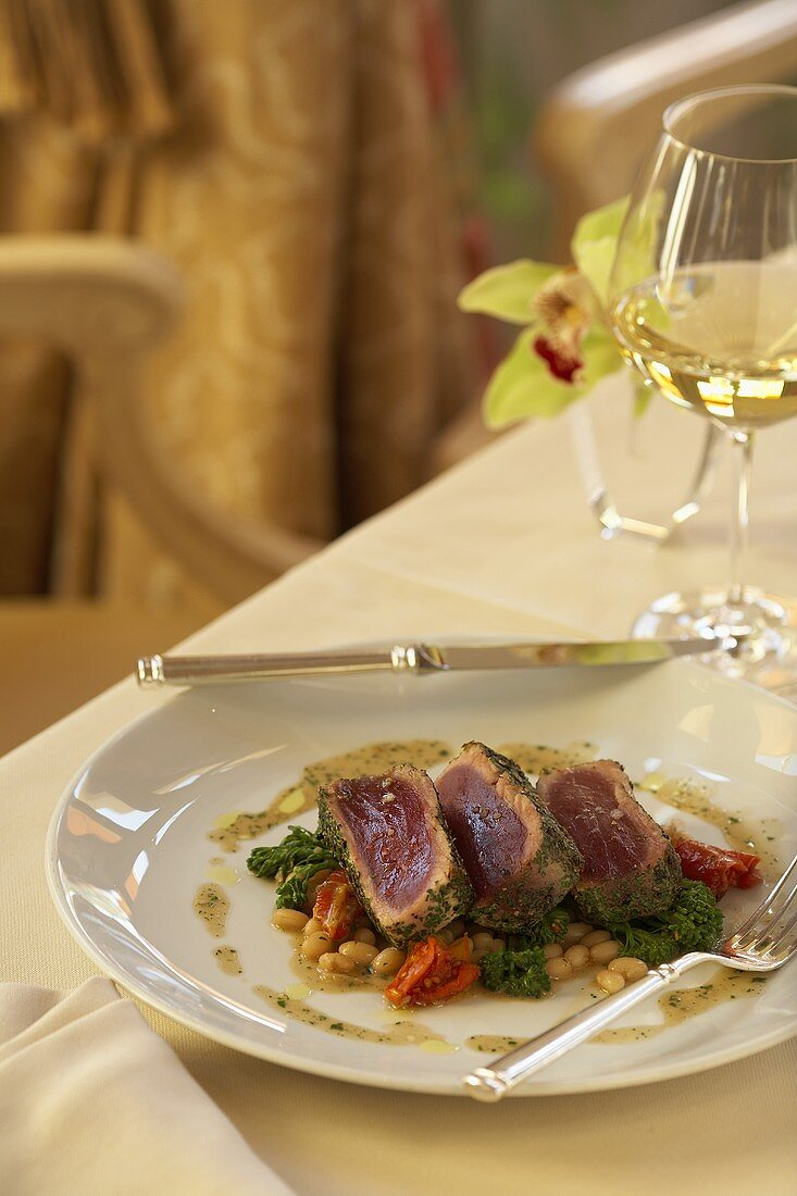 Sliced Seared Tuna on a Bed of Vegetables; On Dining Table with Wine