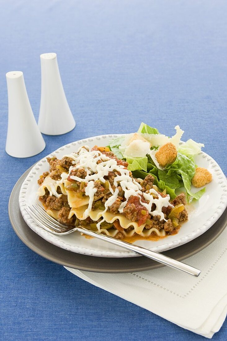 Ground Beef Lasagna and a Side Salad on a Plate with a Fork