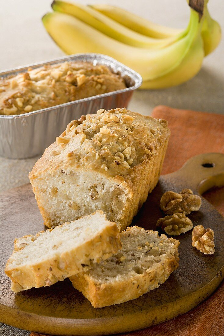 Partially Sliced Banana Nut Loaf Cake; On Cutting Board and Pan