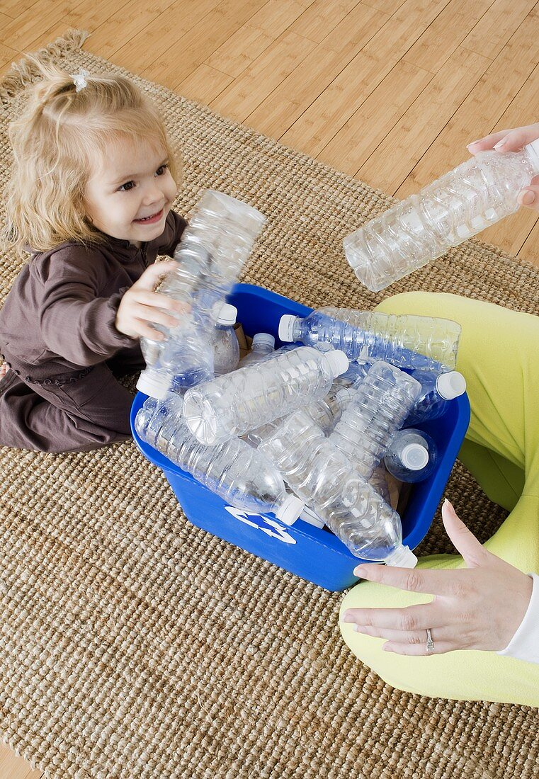 Child and Adult Adding Empty Plastic Bottles to Recycling Bin