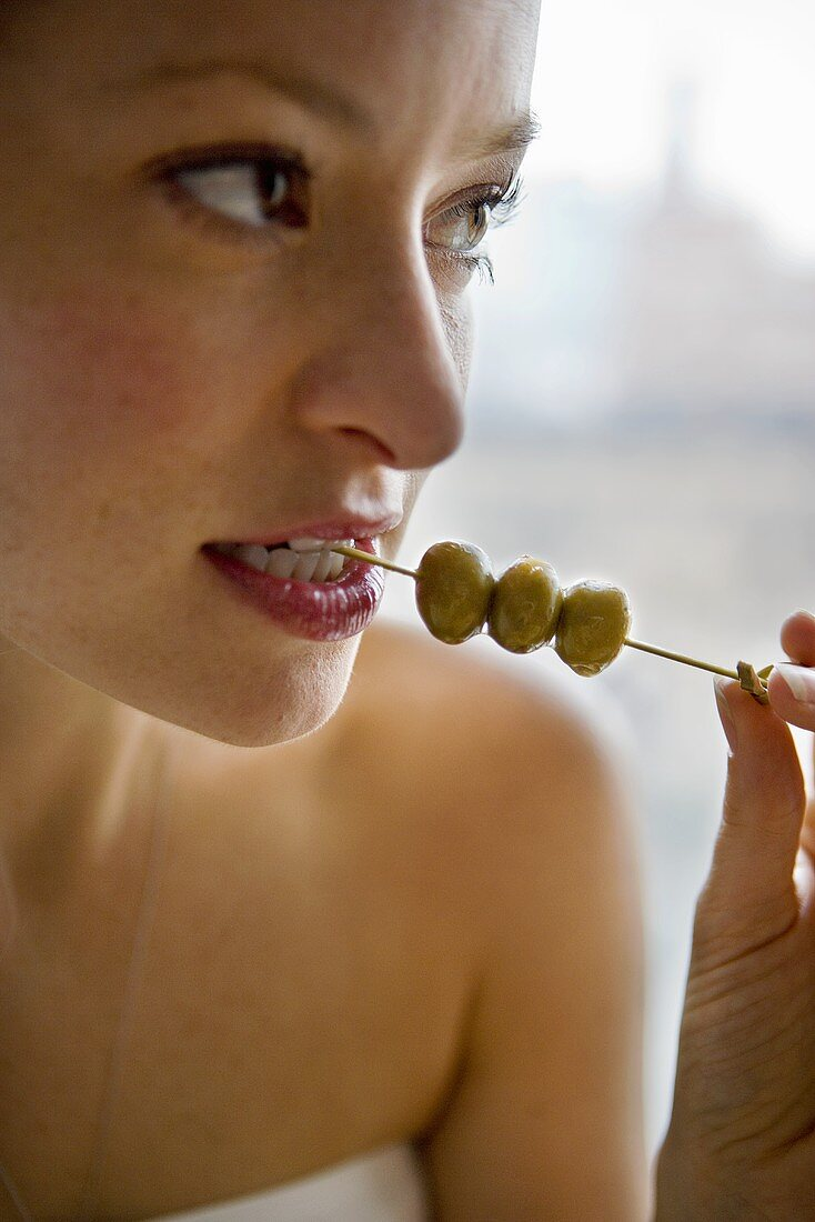 Woman Eating Green Olives off of Toothpick