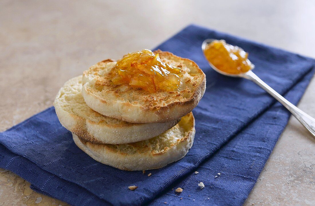 Stacked English Muffin Halves with Marmalade on Blue Towel