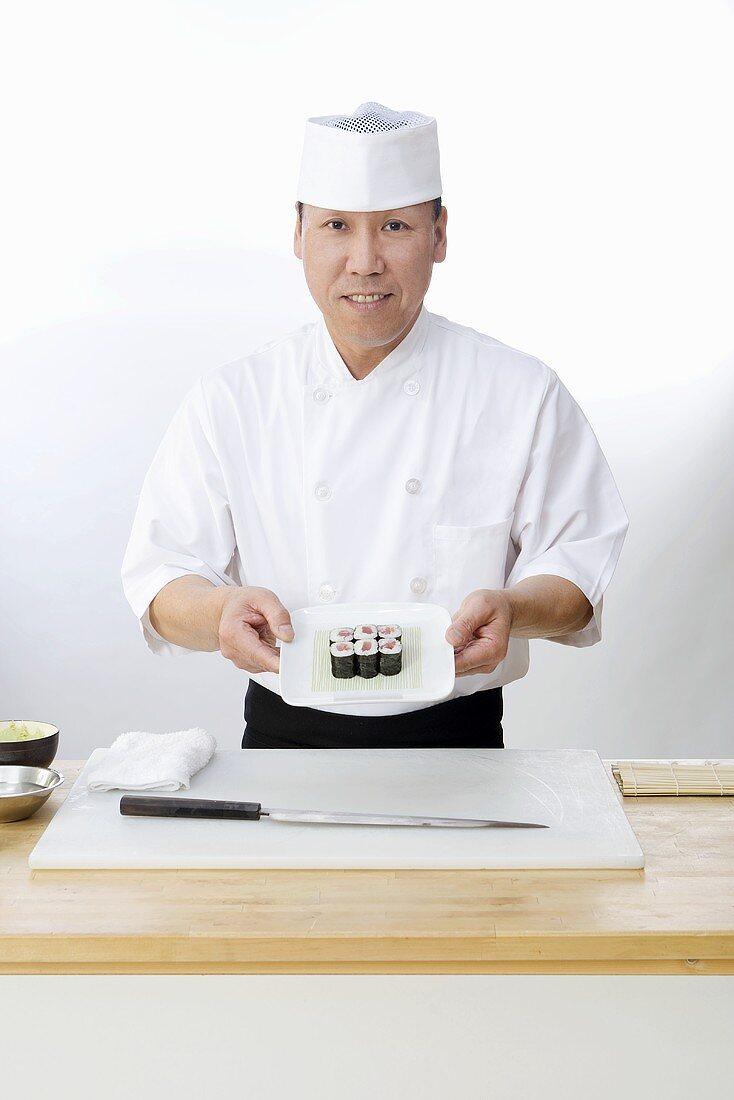 Asiatischer Koch mit Maki-Sushi