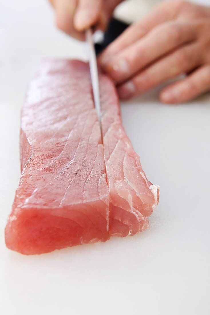Sushi Chef Slicing Raw Ahi Tuna