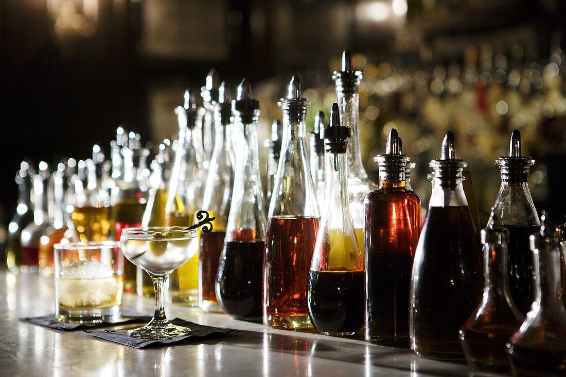 Many Bottles of Alcohol on Bar; Two Cocktails