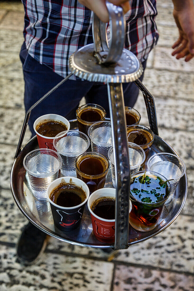 Young man holding a tray with coffee, tea and water in old city, Jerusalem, Israel, Middle East