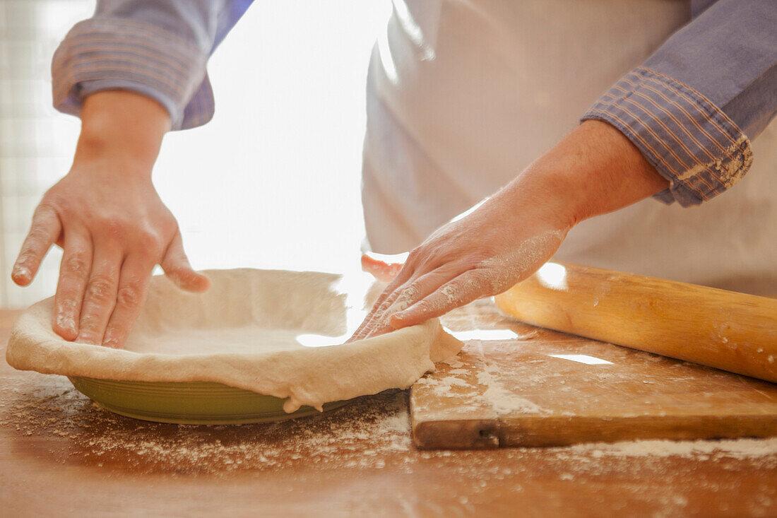 Baker pressing pie dough in dish
