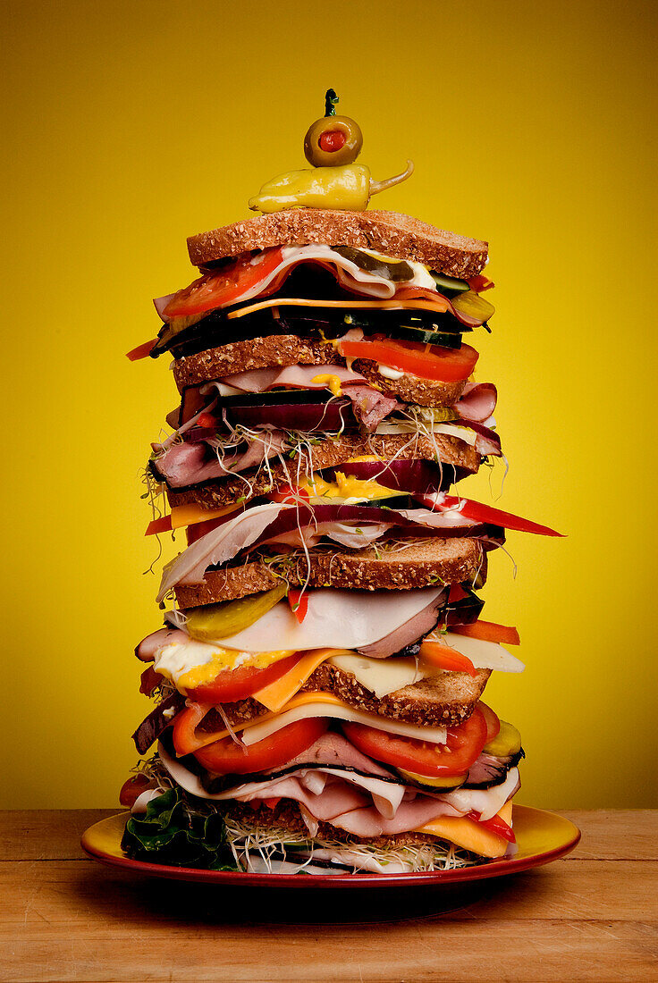 Oversized stacked deli sandwich on plate