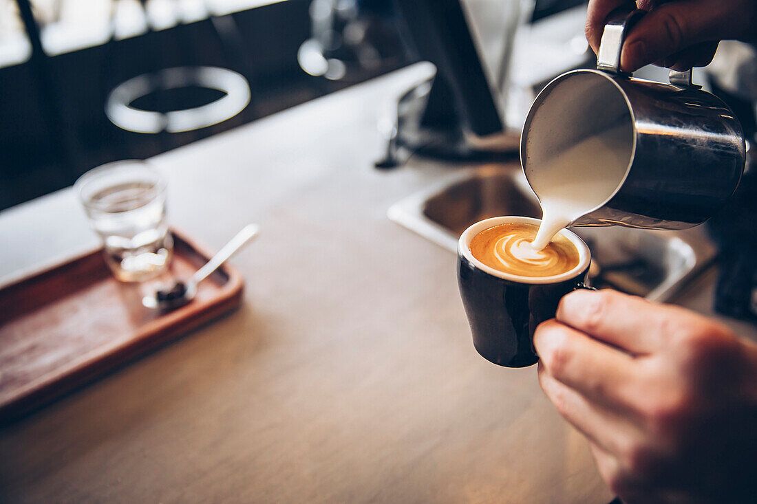Caucasian barista pouring coffee drink in cafe