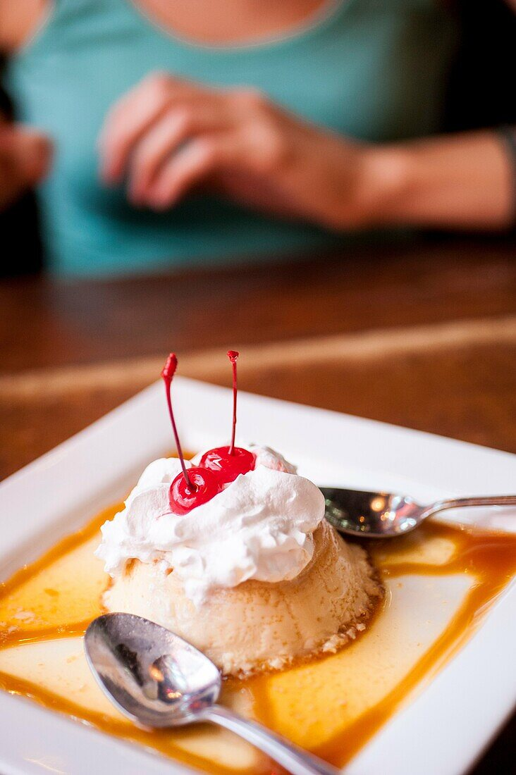 A flan dessert on a plate in a restaurant win a woman´s hands in the background.