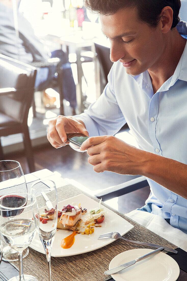 Mann mit Smartphone, um sein Essen im Restaurant zu fotografieren