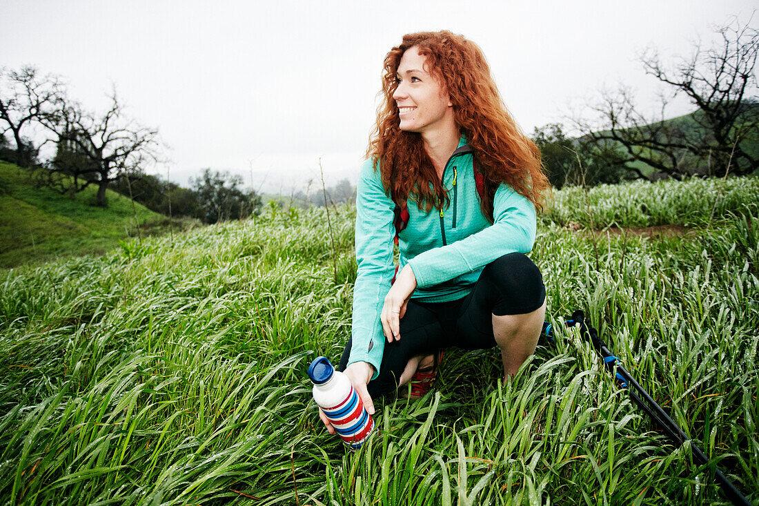 Portrait of crouching Caucasian woman holding bottle