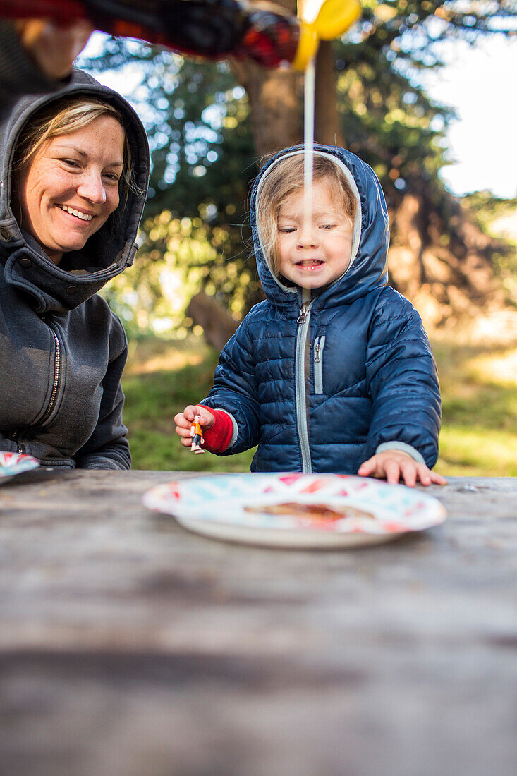 Caucasian mother pouring syrup on pancake for daughter