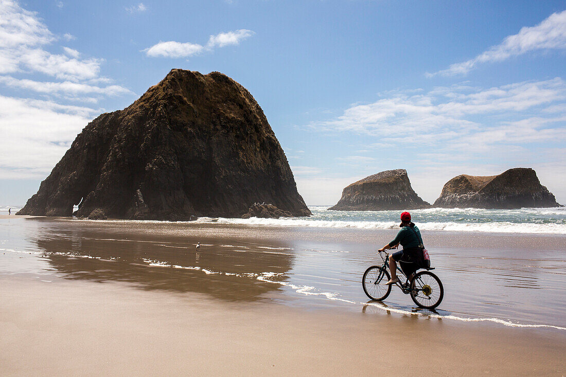 Caucasian woman riding bicycle on beach