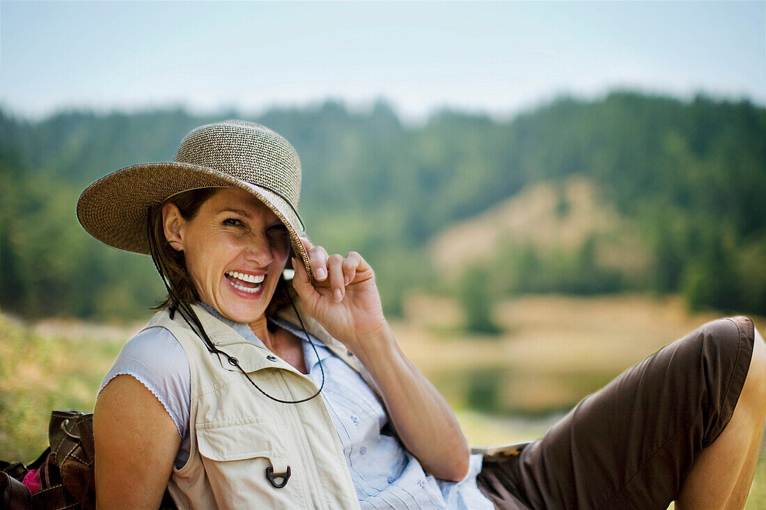 Portrait of playful Hispanic woman pulling brim of hat