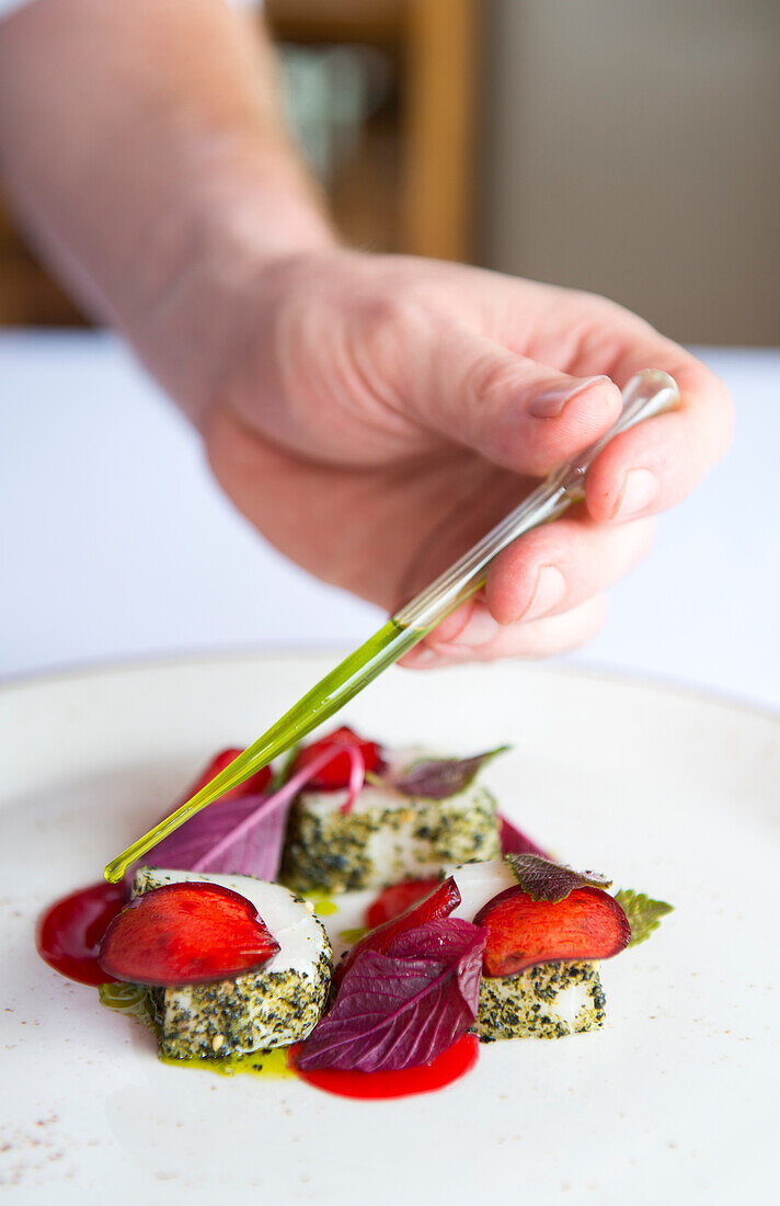 Chef puts finishing touches to sashimi swordfish with plums