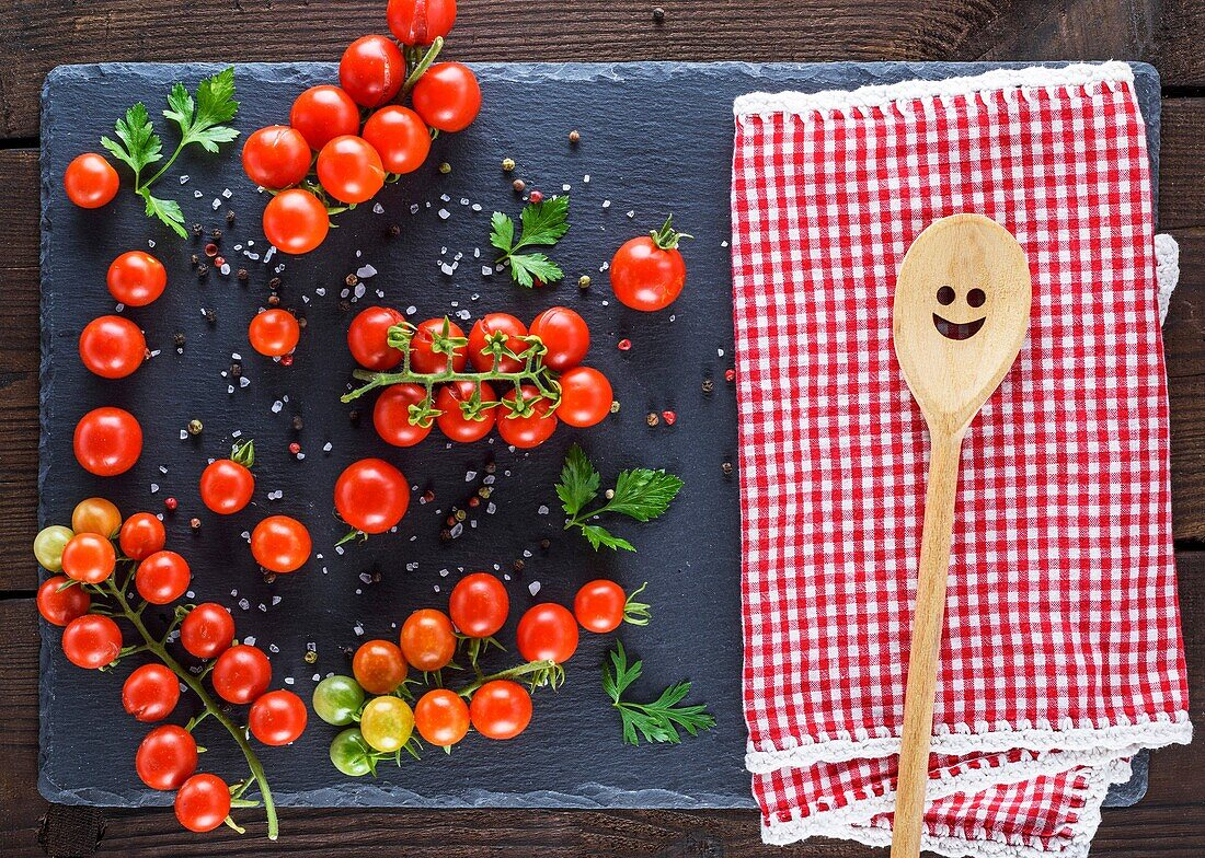 Wooden spoon on a red textile towel and ripe red tomatoes on a black board, top view.