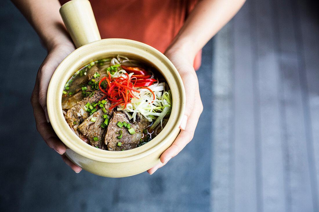High angle close up of person holding bowl of Bun Bo Hue.