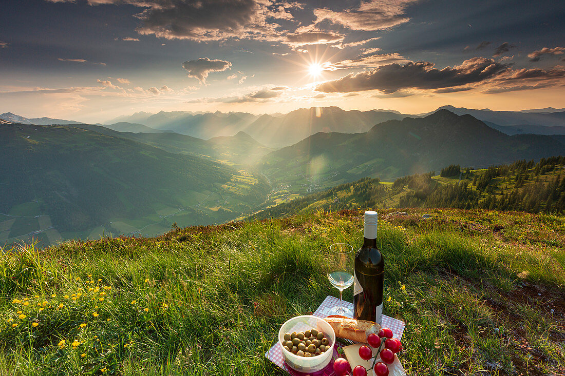 A picnic on the Schatzberg in Alpbach at sunset with a view of the surrounding mountain landscape in Tyrol