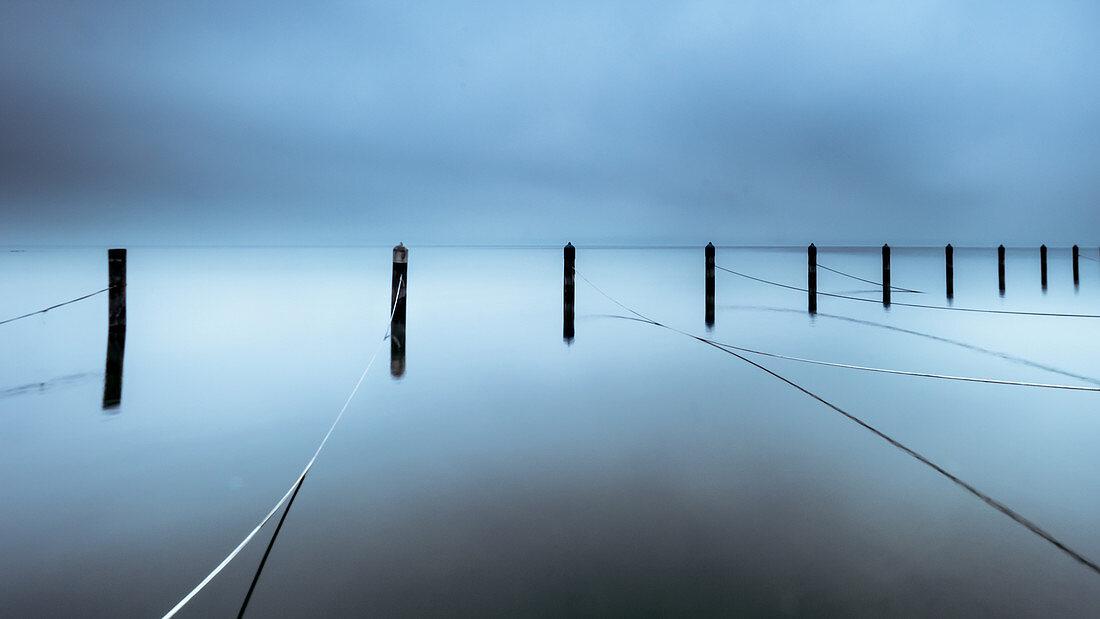Nebliger Wintermorgen in verlassener Marina, Holzpfosten im Starnberger See, Seeshaupt, Bayern, Deutschland