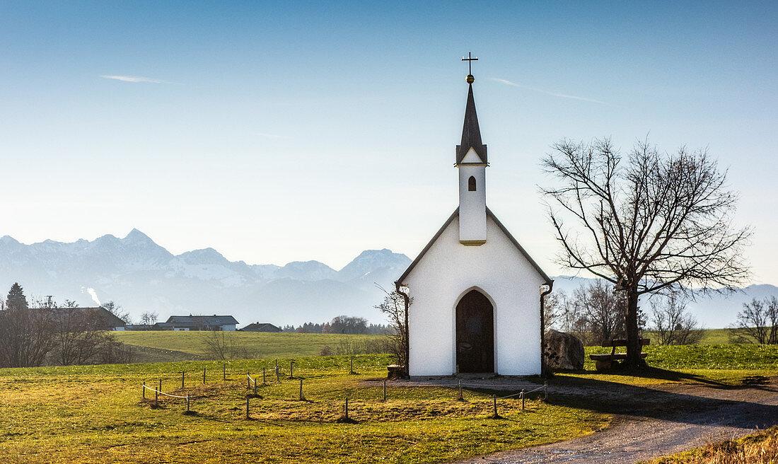 Blick auf Kapelle vor Bergkulisse und blauem Himmel, Söllhuben, Riedering, Bayern, Deutschland