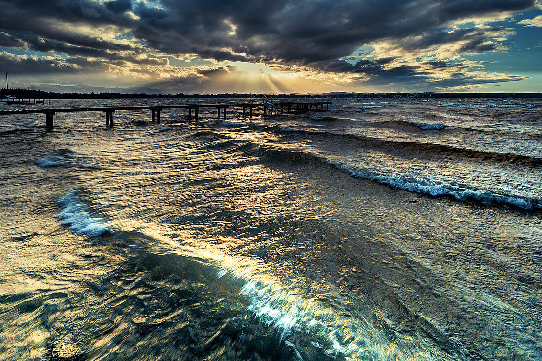 Jetty at sunset in Lake Starnberg with waves, St. Heinrich, Bavaria, Germany