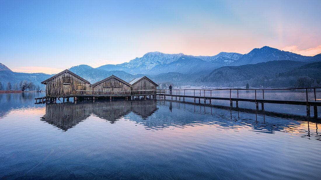 Bootshütten bei Sonnenuntergang am Kochelsee mit Steg, Schlehdorf, Bayern, Deutschland