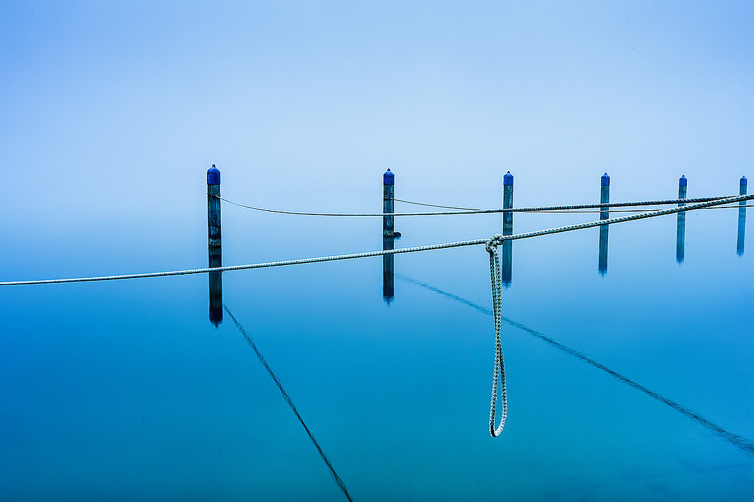 Ropes on wooden posts in the abandoned harbor in winter in Lake Starnberg, Seeseiten, Bavaria, Germany