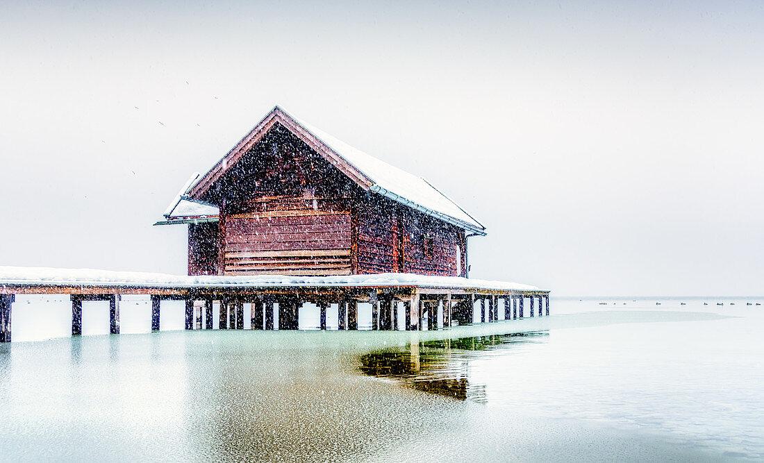 Boathouse during snowfall on Lake Starnberg, Tutzing, Bavaria, Germany