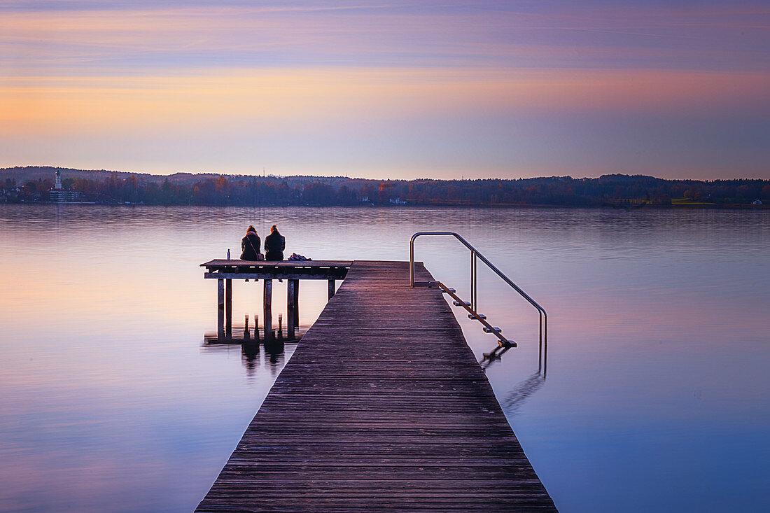 Zwei Frauen sitzen auf einem Steg und schauen auf den Starnberger See, Bayern, Deutschland