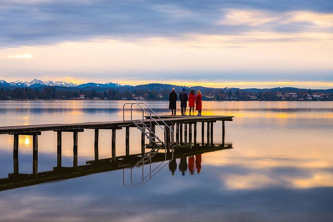 Steg mit Leuten am Starnberger See bei Sonnenuntergang  mit Blick auf die Berge, St. Heinrich, Bayern, Deutschland