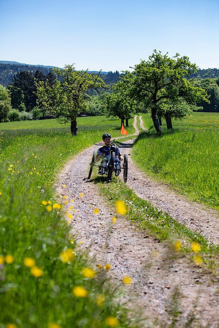 Mann fährt Fahrrad für Querschnittsgelähmte auf Feldweg durch üppige Frühlingswiese, Heimbuchenthal, Räuberland, Spessart-Mainland, Franken, Bayern, Deutschland, Europa