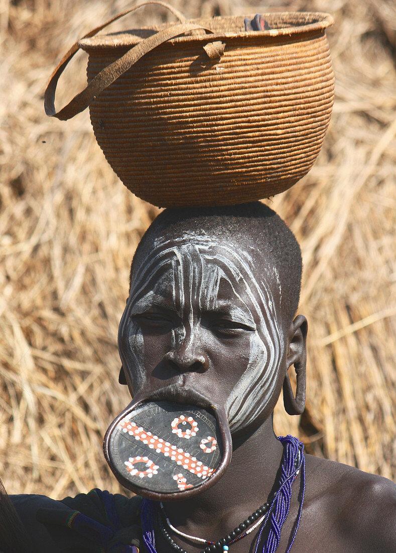 Äthiopien; südliches äthiopisches Hochland; Mago Nationalpark; Omo Fluss; junge Mursi Frau mit traditionellem Lippenteller und Gesichtsbemalung; Lippenteller aus Terrakotta mit gemalten und geritzten Mustern